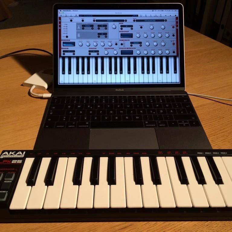 Keyboard Tastatur vor Laptop, auf welchem diese Tastatur ebenfalls zu sehen ist. Darüber befinden sich mehrere virtuelle Schalter und Drehregler, um den Klang zu wählen und anzupassen.