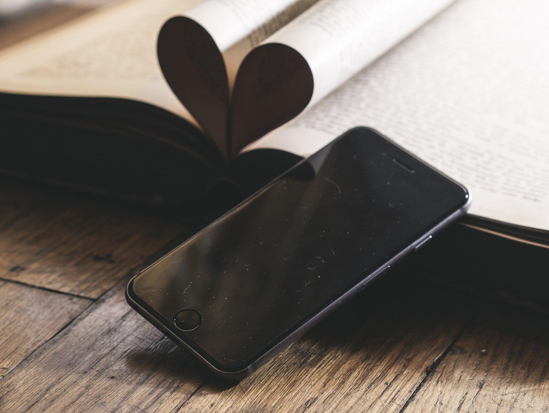 Smartphone vor Buch, dessen Seiten zu einem Herz gefaltet sind